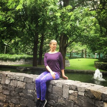 Karen Webb Green in seated twist position on a wall surrounded by trees and water