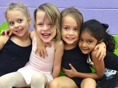 four girls hugging dance class studio Austin Texas