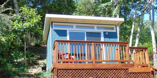 A room with a view this home office studio shed sits on a wooded hill side with a redwood deck.