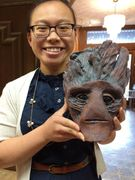 a sculptor holding her sculpted Groot head