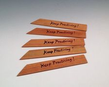 simon leach throwing sticks that say keep practicing