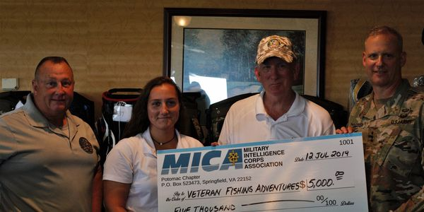 Ed Moore, program founder & daughter Holly Moore accept a MICA check from MG Potter and LTG Berrier