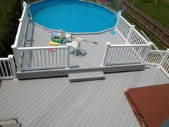 Gray VEKA Deck with White Vinyl Railing. Around a Swimming pool.