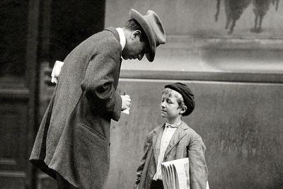 A man writes a note for a newspaper boy.