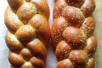 2 loaves of braided challah bread, one with sesame seeds and one with poppy seeds