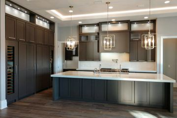 Contemporary kitchen with large oversized pendant lights and built in subzero columns.