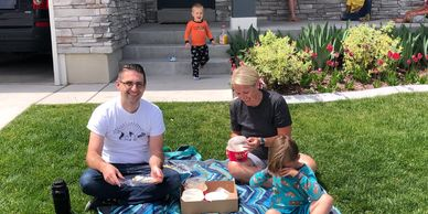 Neighborhood delivery of Suzy Thai Food Utah Family eating on lawn at home during Covid-19 pandemic.