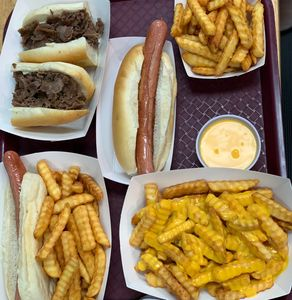 Dinner from The Hot Stop, A cheese steak, hot dogs, cheese fries and french fries on a tray to dine in