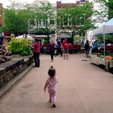 Child walking through Farmer's Market at the Fayetteville, Arkansas square featuring small business