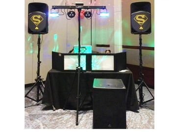 dance floor laser lights, bass cabinets and 2 loud speakers, plus laser-lit all-black DJ setup.
