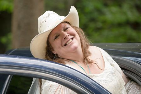 Owner in profile picture in Western attire outside getting in her vehicle.