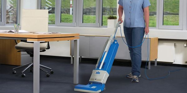 Technician vacuuming as part of Office Cleaning Service.