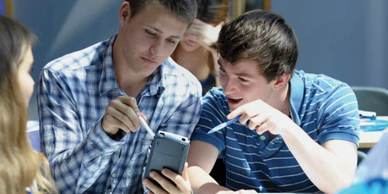 man and boy looking at a mobile phone
