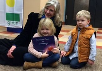 Mary sits with two children, excited about their new book.