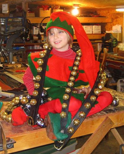 """child elf dressed in costume with long strap of brass reindeer sleigh bells draped over shoulder"""