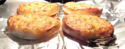 English muffins covered with bubbly melting cheese combined with garlic cheese sprinkle mixture