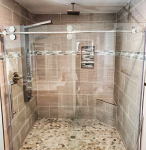 Custom Tile Shower With Rainfall Shower Head and Glass Door. By Lavish Builders Lansing Home Builder