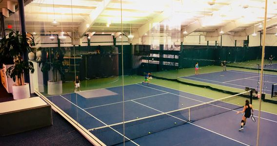 Glass enclosed lobby provides direct viewing to the tennis courts and tennis players.