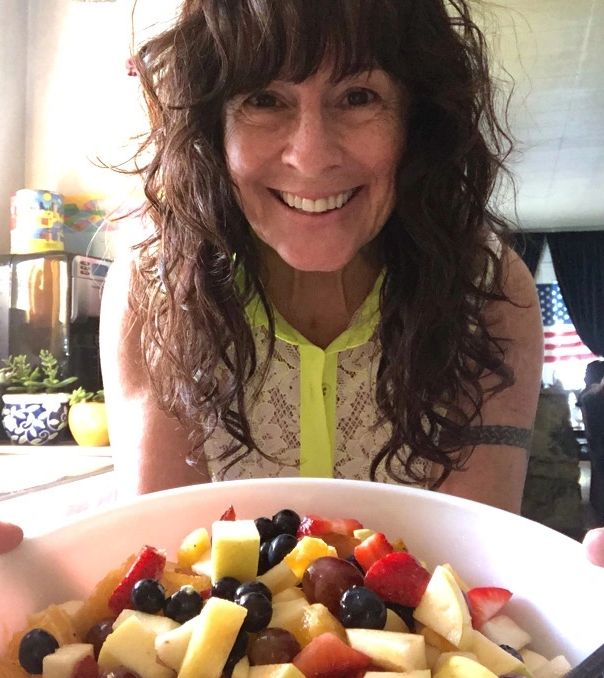 Coach Julie Beck as an online personal trainer nutrition coach showing her homemade fresh fruit bowl
