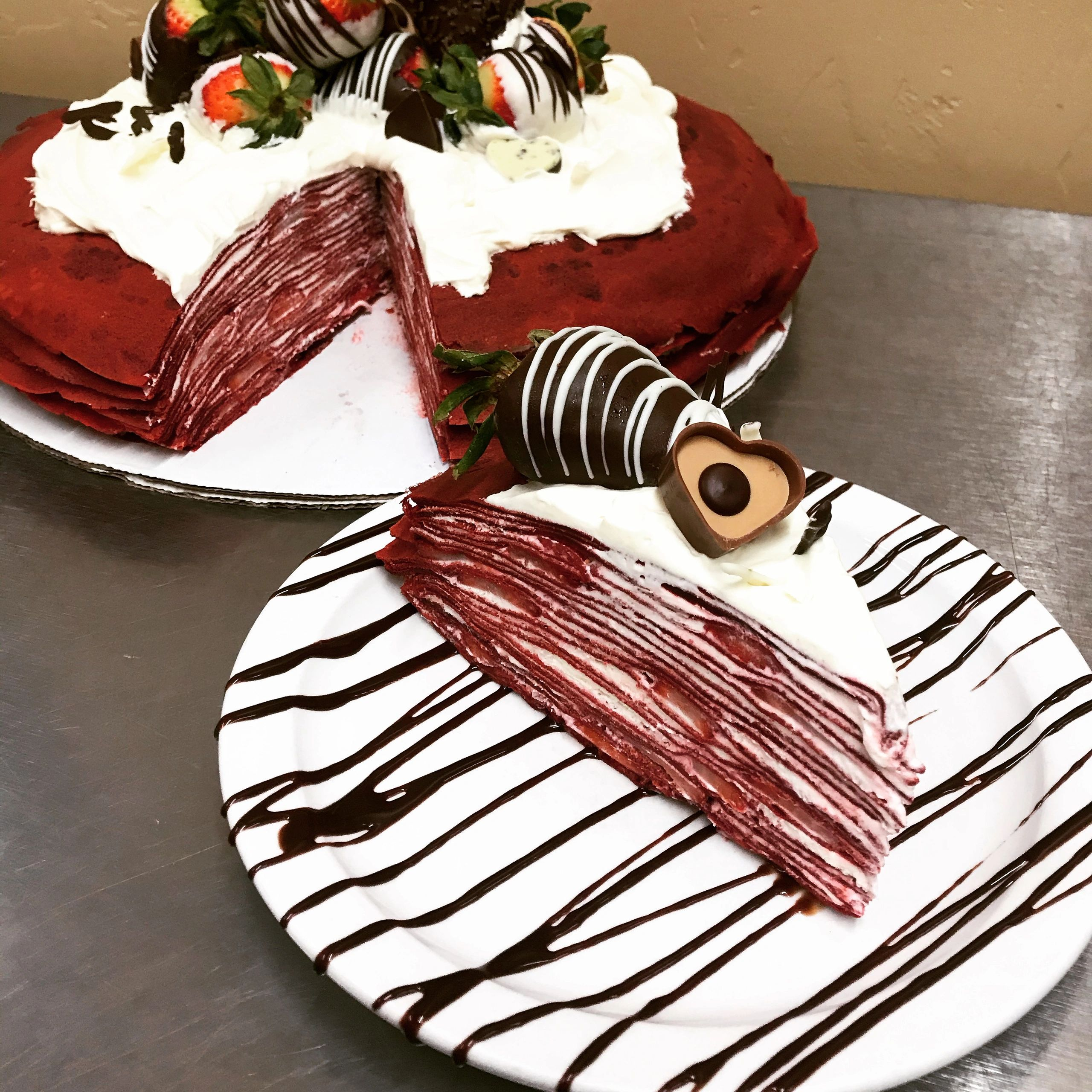 Slice of red velvet crepe cake with 20 layers of paper thin crepes