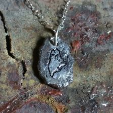 Maine in the raw.  Sterling silver pendent.