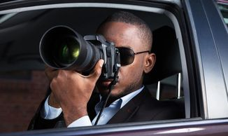 Private Investigator sitting in car using a camera with a telescopic lens.
