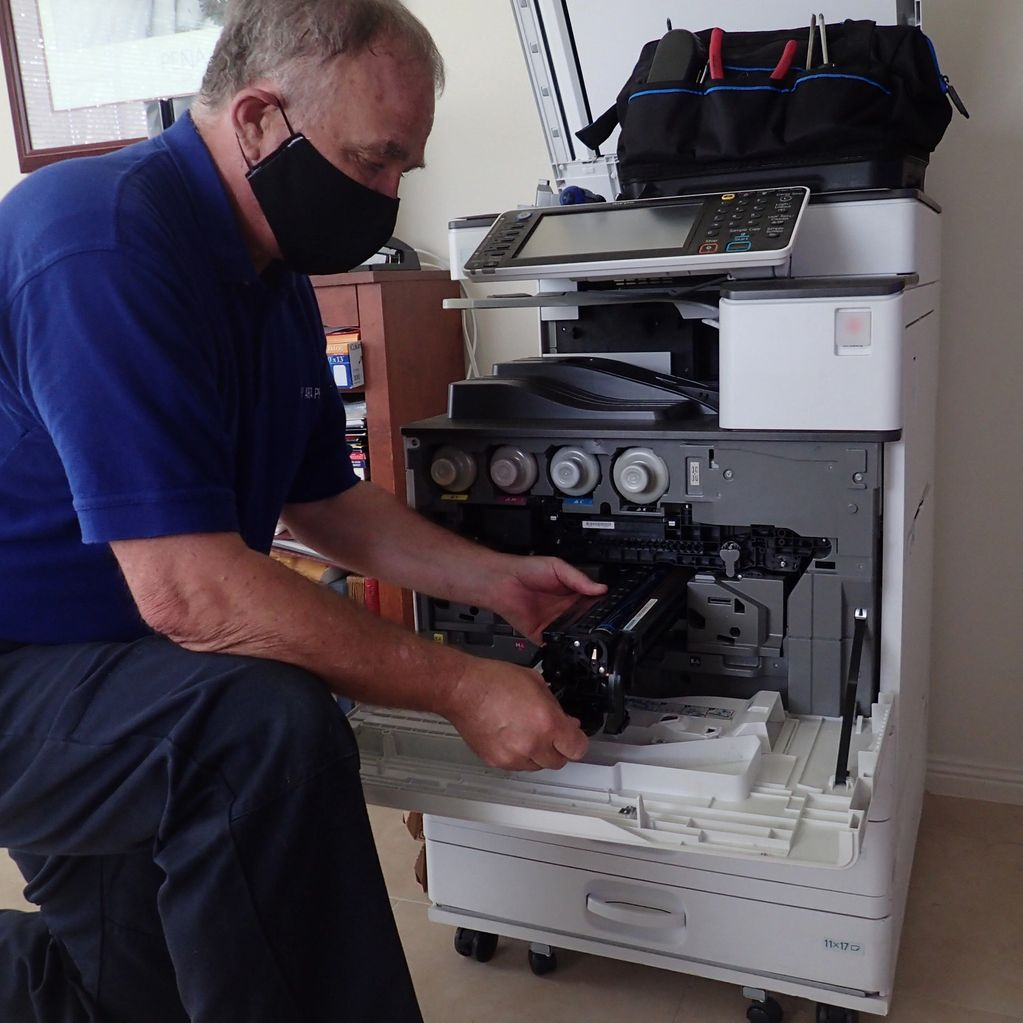 Technician working on Ricoh C2003 multi-function copier.