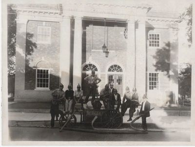 Members of the Hercules Hose Co. No. 1 pose in front of a hand pump parked in front of old Town Hall