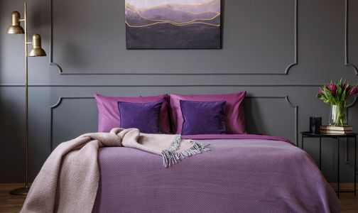 A bedroom with bed linens, flowers and a painting in various shades of deep purple