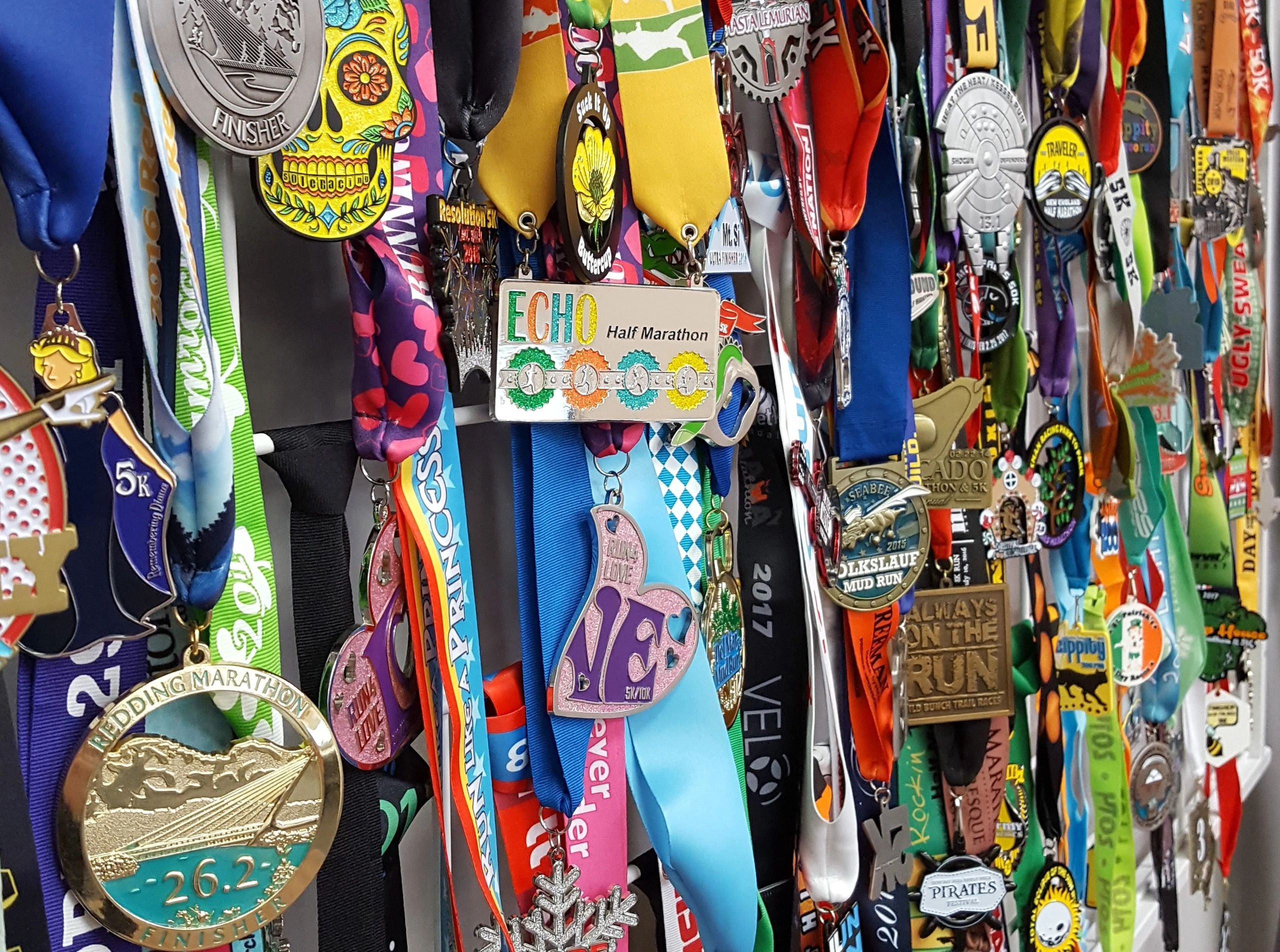 Wall of hanging colorful race medals and custom race ribbons from many running event brands.