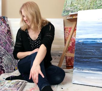 Abstract artist Lisa Hayden in her art studio with artwork on canvas