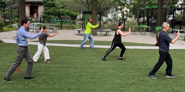A group of 5 people practice Tai Chi in a park.