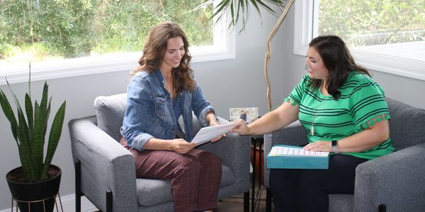 Two women in chairs talking - Certified Enneagram Coach conducts in person coaching session.