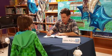 The Friends support the BiblioArte Festival - picture of John Para signing his book for a child