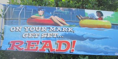 Banner of two children floating on a river with the caption On you mark, get set, Read!