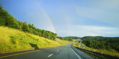 Double rainbow over green forest and highway.