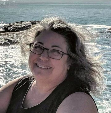 Smiling woman with grey hair and black glasses in front of water.