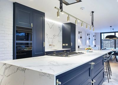 Navy blue kitchen with marble slab backsplash countertop and island