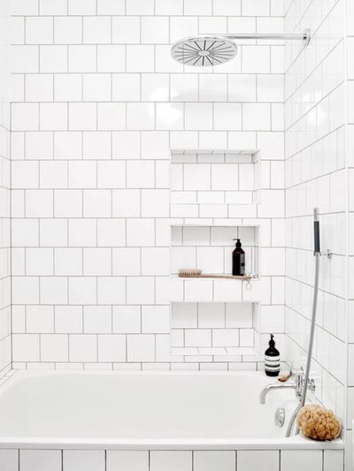 bathroom remodel with built-in shampoo soap shower niches tiled with white square subway tile
