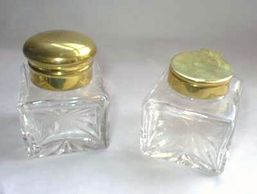 Pair of ink bottles showing the dome and flat flip tops in brass