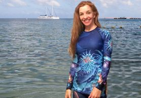 "Coral themed rash guard for women ""Bubbles & Blues"" woman standing in ocean Living Sea Sculpture"