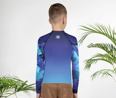 "back view of boy's rash guard ""a purple urchin sunset"" with Living Sea Sculpture logo"