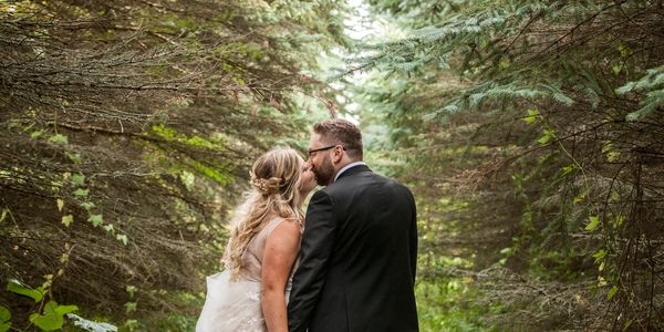 A bride and groom kissing on a path in the forest lined with trees