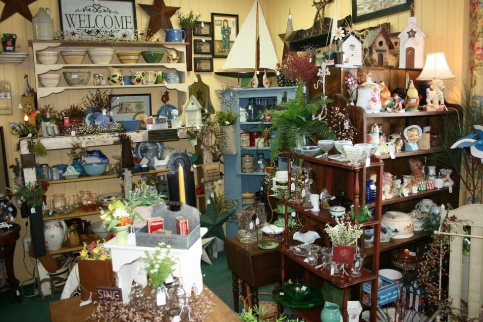 Antique welcome sign with variety of antique items in store