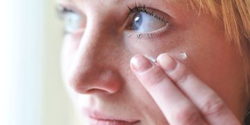 Woman applying cream near her eye