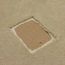 A large square has been cut out of a beige carpet, showing the underlay underneath