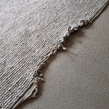 The edge of a rug has become badly frayed and untidy