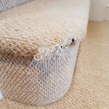 The carpet on the edge of a stair has a hole surrounded by fraying fibres due to pet damage