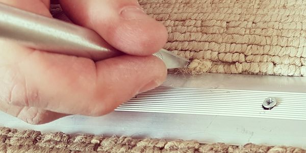 A carpet repair technician's hand moving carpet fibres using a specialised tool