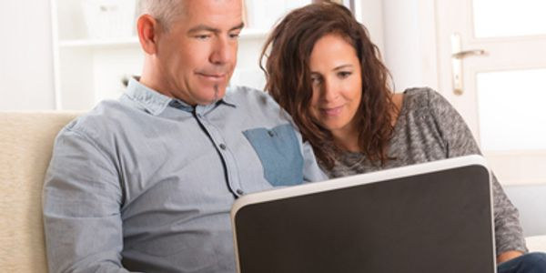 man and woman on a couch looking at a computer receiving online couples coaching
